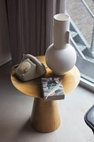 Large modern vase and vintage telephone on small wooden side table