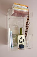 Clear perspex wall mounted shelf with books and glassware
