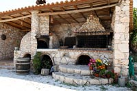 Stone barbecue and pizza oven on covered terrace