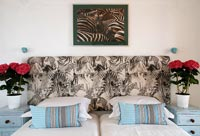 Modern bedroom zebra patterned headboard and photograph above bed