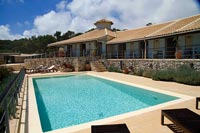 Recliners next to swimming pool next to villa