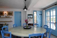 Blue painted chairs around circular wooden dining room