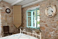 Country bedroom with exposed stone wall and maritime themed mirror