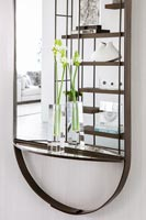 Cut flowers in glass vases on mirror ledge with reflection of modern shelving