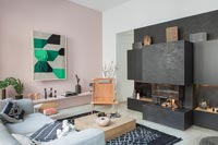 Black contemporary fireplace in modern living room with pink painted feature wall