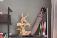 Sculpture and quill filled with arrows on bookshelves