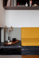 Yellow sofa cushions on built-in seat within alcove with surrounding shelving
