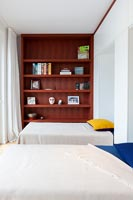 Twin beds and wooden bookcase in modern bedroom