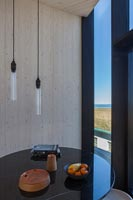 Small circular table and bare pendant lighting next to window with coastal view