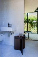 Black side table in modern bathroom with view to bedroom window
