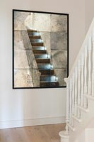 Antique mirror reflecting stairs in modern hallway