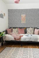 Patterned feature wall in modern bedroom with daybed