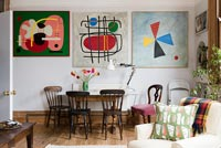Dining area and wall of colourful modern artwork in open plan living space