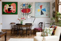 Dining area and wall of colourful modern artwork in open plan living space. 