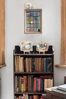Vintage wooden bookcase with modern painted ceramics on shelf