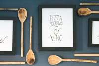 Framed picture surrounded by wall mounted wooden spoons on kitchen wall