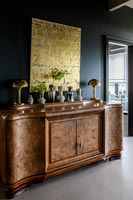 Vintage wooden sideboard with display of vases and gold painting