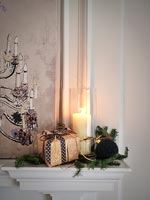 Christmas gift, decoration and lit candle on mantelpiece