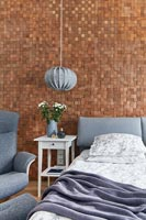 Modern bedroom with textured exposed mosaic brick wall