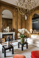 Classic wooden panelled living room with textured chandelier