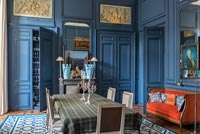 Dark blue painted panelled walls in classic style dining room