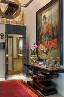 Large classic painting and unusual console table in hallway