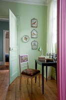 Green painted walls and pink curtains in bedroom