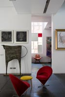 Small red chairs with yellow stool side table surrounded by modern artwork