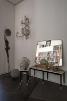 Mirror on side table with sculptures
