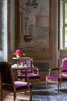 Purple antique chairs with huge painting on wall in class living room