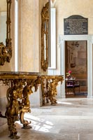 Pair of gilded console tables with mirrors in classic hallway