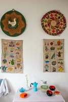 Decorative wall hangings above small table