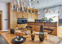 Modern wooden kitchen diner with rose coloured light fittings