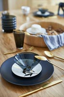 Black, white and gold crockery on dining table - detail