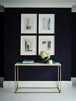 Metal table and display of artwork on black painted wall