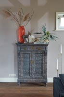 Grey painted wooden unit decorated with white writing
