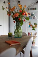 Red and orange cut flower arrangement in vase on dining table