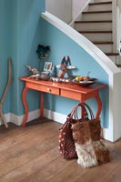Small wooden console table at bottom of staircase