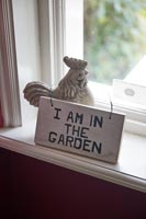 Wooden sign and chicken ornament on windowsill