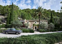 Exterior of stone country house with vintage car parked in driveway