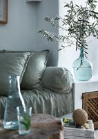 Blue glass vase of olive tree branches on side in modern country living room