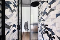 Modern wet room with patterned tiling on wall