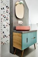 Teal and pink sink unit against concrete wall in modern bathroom