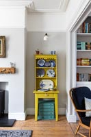 Small yellow painted dresser with display of blue and white plates