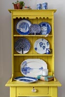 Yellow painted small wooden dresser with display of blue and white plates