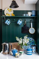Blue and white crockery in modern kitchen with green painted wall