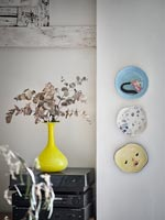 Display of ceramic plates on wall next to yellow vase