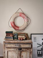 Lifebuoy on wall above distressed cabinet