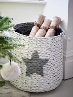 Basket of Christmas crackers next to tree