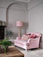 Pink sofa and floor lamp next to grey painted wall